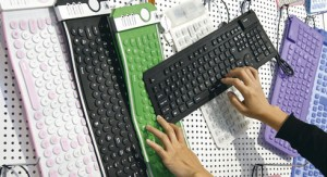 Woman touches a flexible rubber made keyboards at IFA consumer electronics fair in Berlin